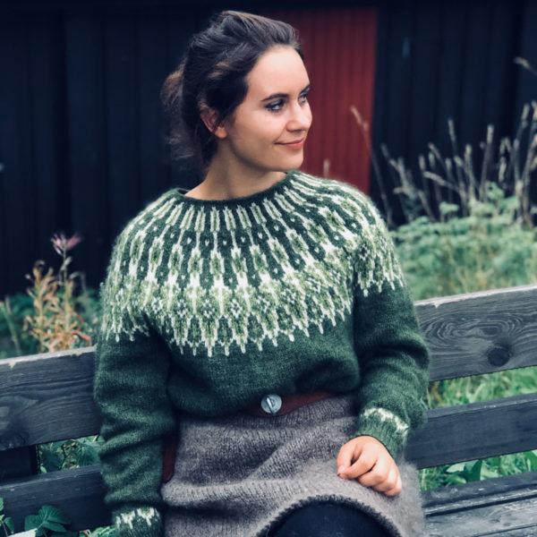 Jente som sitter på en benk ikledd en olivengrønn og grå strikkegenser av typen villmarksgenser