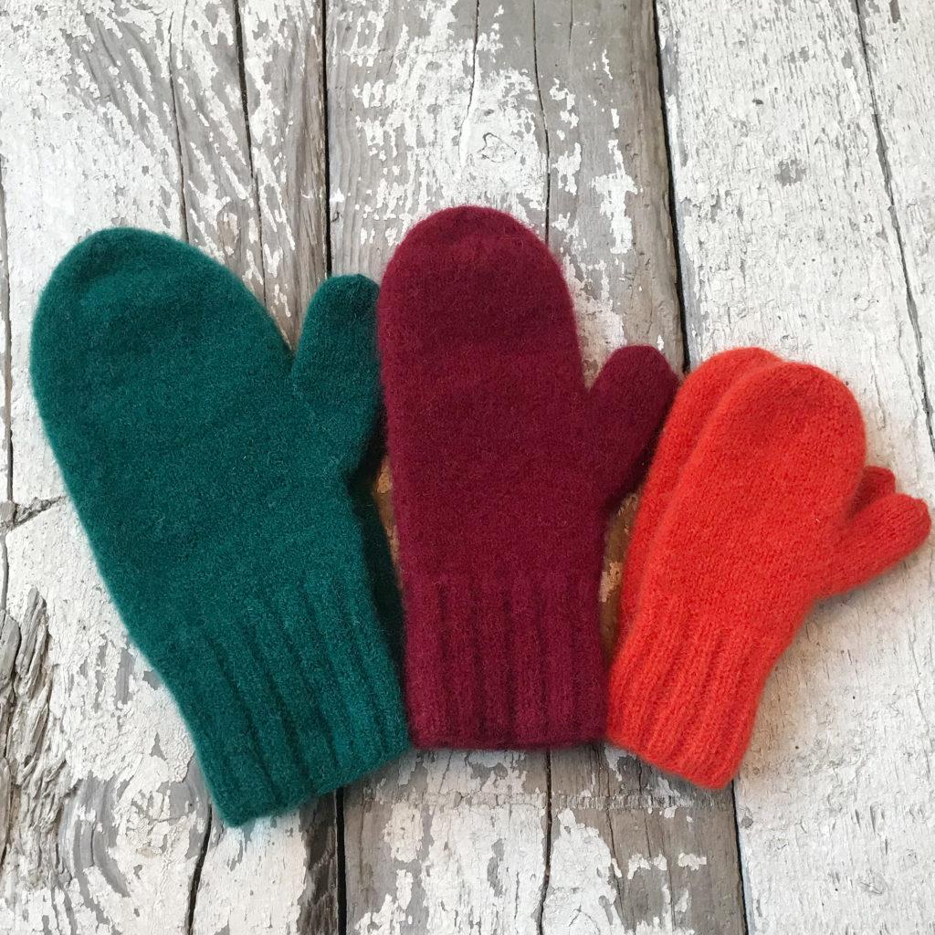 tre strikkete votter i grønn, rød og oransje