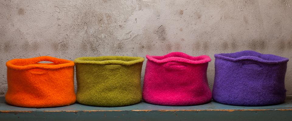 Fire tovede ullkorger. En oransje, en grønn, en rosa og en lilla.